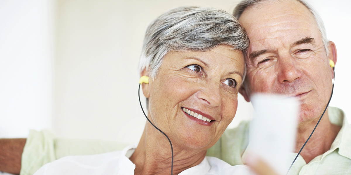 Closeup of happy mature couple listening music together at home