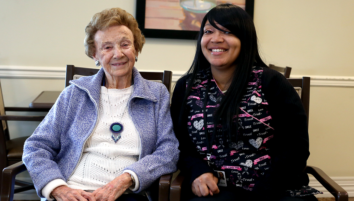 Personal care resident and aid smiling together